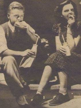 School hours sometimes vary with studio requirements. But this day Judy Garland and Mickey Rooney were in school at the noon hour, and, like village students, sat on the schoolhouse steps as they ate their lunch.