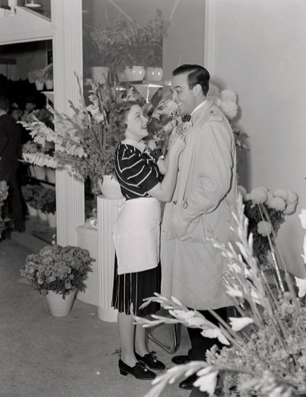 """Judy Garland and director George Sidney in her flower shop, """"Judy Garland Flowers"""" early 1939"""