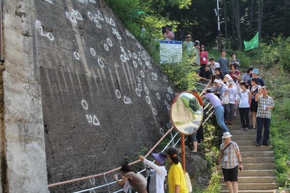 "Scholars visit the scene of a massacre and peace park at Nogeun Village in Yeongdong, North Chungcheong Province on June 29 as part of their when a 60th anniversary ""peace journey"" to Korean War sites around the country, held from June 28 to July 2. In the Nogeun massacre, 163 Korean villagers were killed as they fled by US soldiers. (by Kim Bo-geun)"