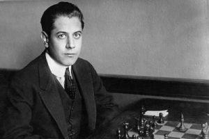 Jose Raul Capablanca mirado a la cámara mientras juega al ajedrez