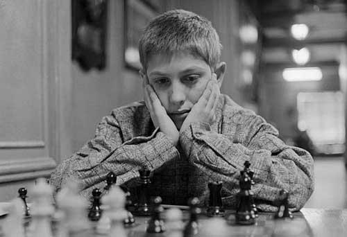 Bobby fischer joven jugando ajedrez tocándose las mejillas con las manos.