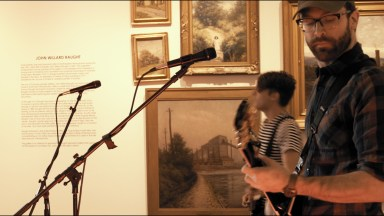 "Doug Griffiths plays in front of a wall of canvas art at the Everhart Museum during a performance of James Barrett's ""Something New."""