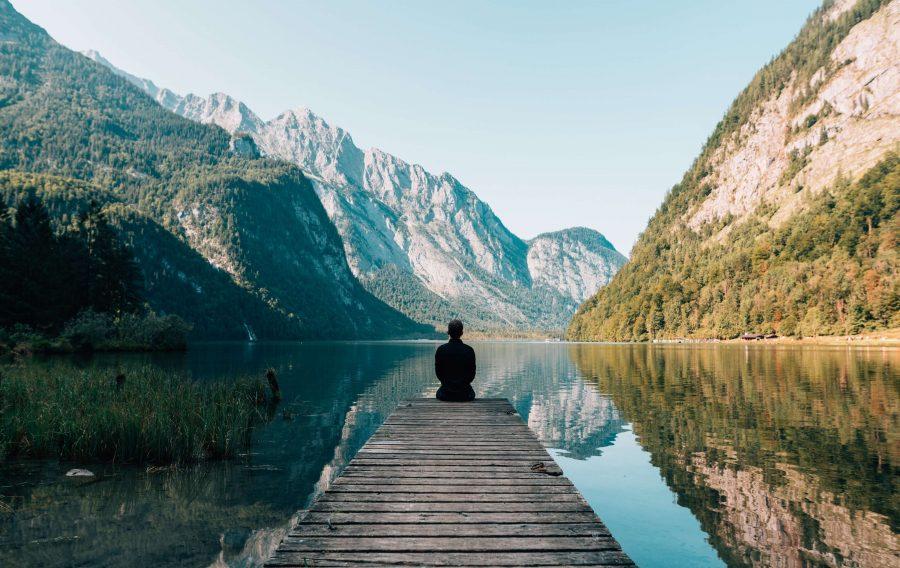 header 4 apps de bien-être self care, homme qui médite dans la montagne devant lac