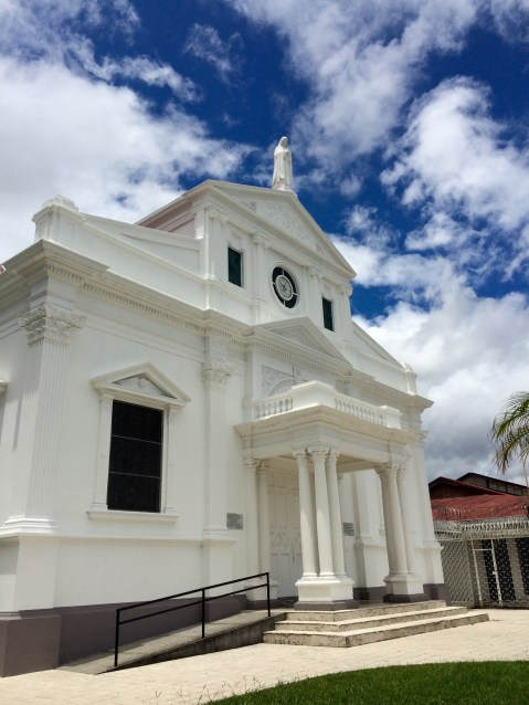 The pearly white facade of this church contrasts with the blue cloudy sky