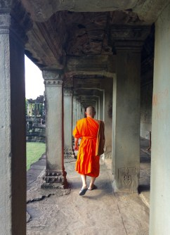 A Buddhist monk walking the aisles of Angkor Wat