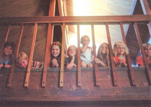 8 children peering through banister
