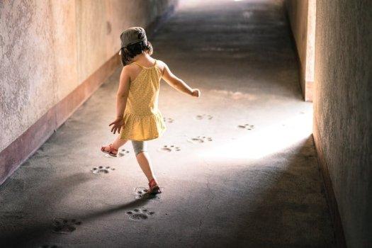 Little girl follows big cat pawprints