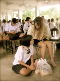 A Thai student respectfully sits at the feet of her mother on Mother's Day
