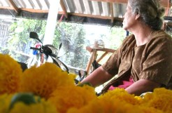 Yai takes a break from stringing flowers. She carries a fierce beauty with rough edges from years of farming.