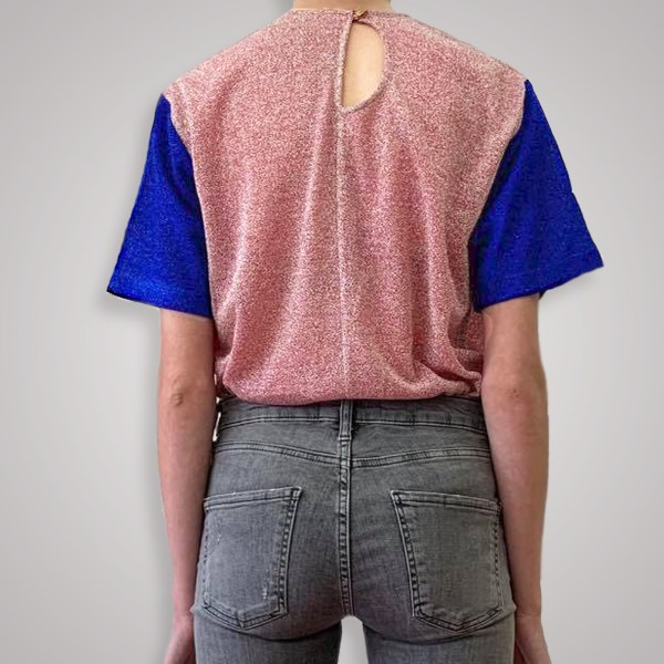 Two toned shirt from behind on woman with open loop back showing. In pink and blue metallic two tones.