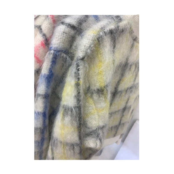 mohair sweaters in soft cream color with yellow, blue and pink plaid patterns on a shopping rack.