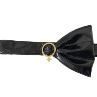 Fairy bow party belt is made of black vinyl and has an asymmetrical bow on the right side of its buckle. The buckle is made of white gold and is shaped like the female symbol.