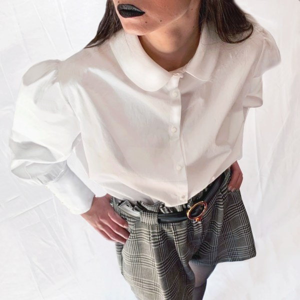 Downwards photo of white cotton blouse on a model also wearing jacquard shorts with black leather belt with white gold buckle. Model is wearing black lipstick and has her hands on her hips.