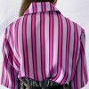 Back of the striped women's silk striped blouse in pink and purple vertical stripes. The silk top is tucked into jacquard shorts and a black belt.