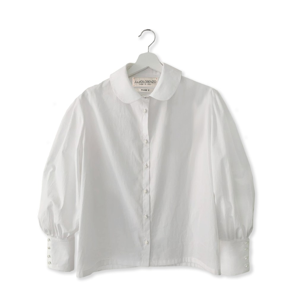 White cotton blouse with white collar and white pearl buttons going up the blouse and on its cuffs. Peter Pan style women's long sleeve blouse.