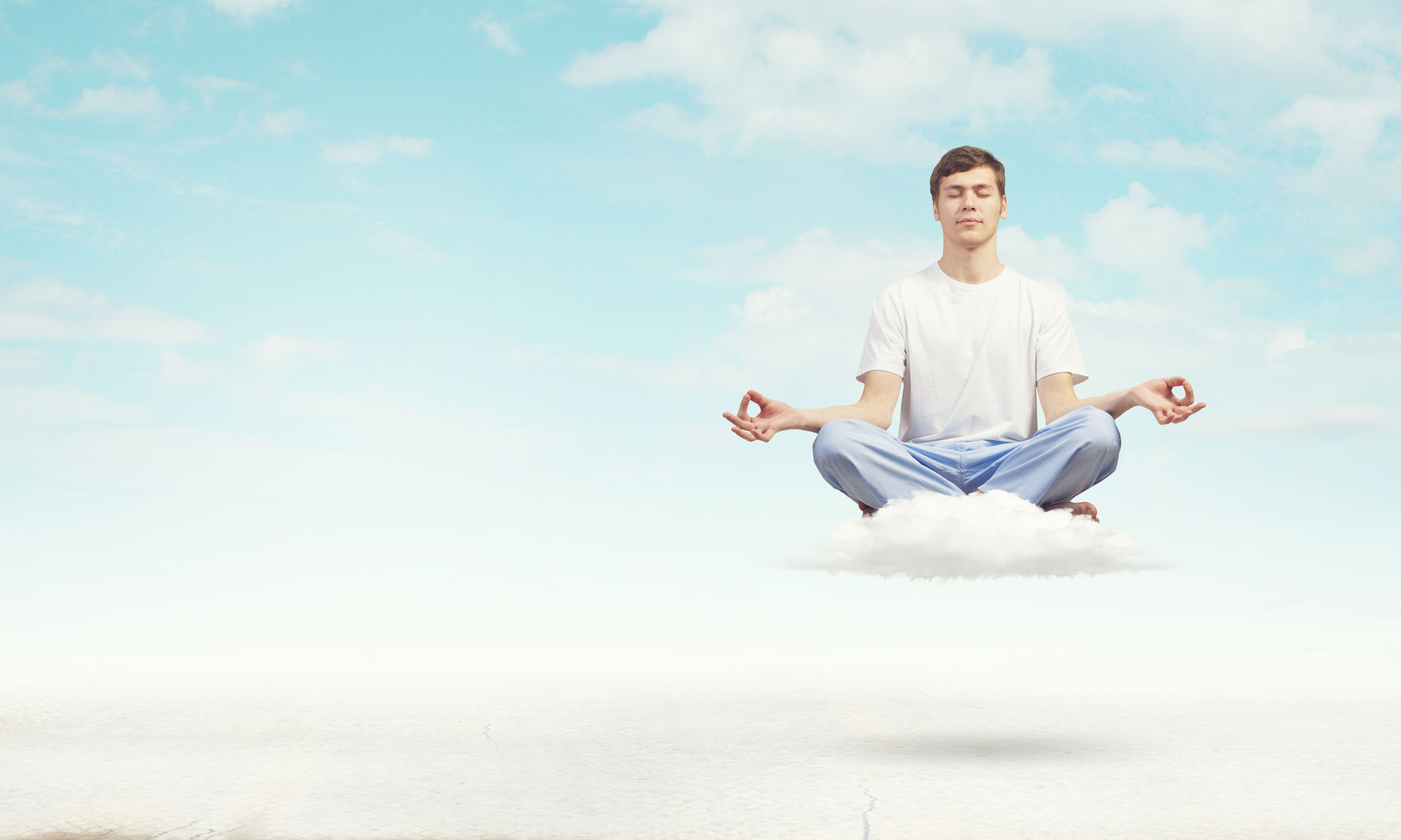 Young man meditating in the clouds.