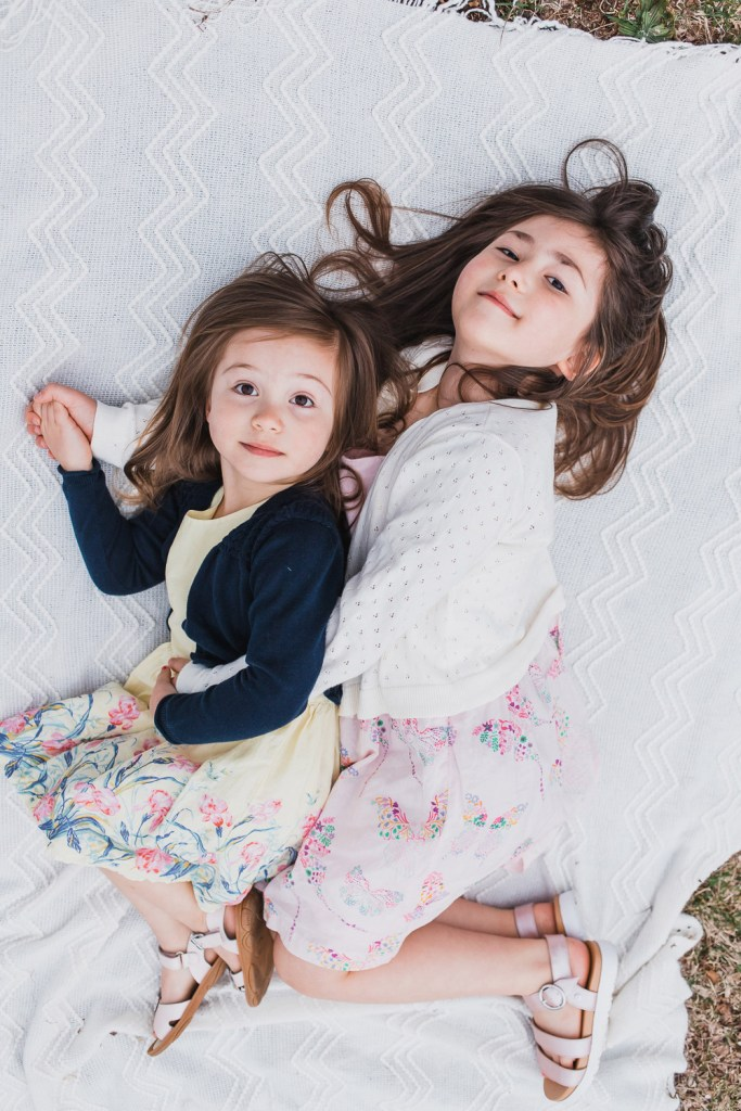 Sibling photo. Two girls embracing each other on a picnic blanket.