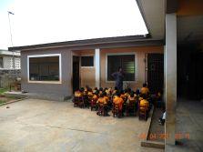 Der Kindergarten findet morgens oft draußen statt. Rechts ist die Tür zur Bibliothek, links die Küche.