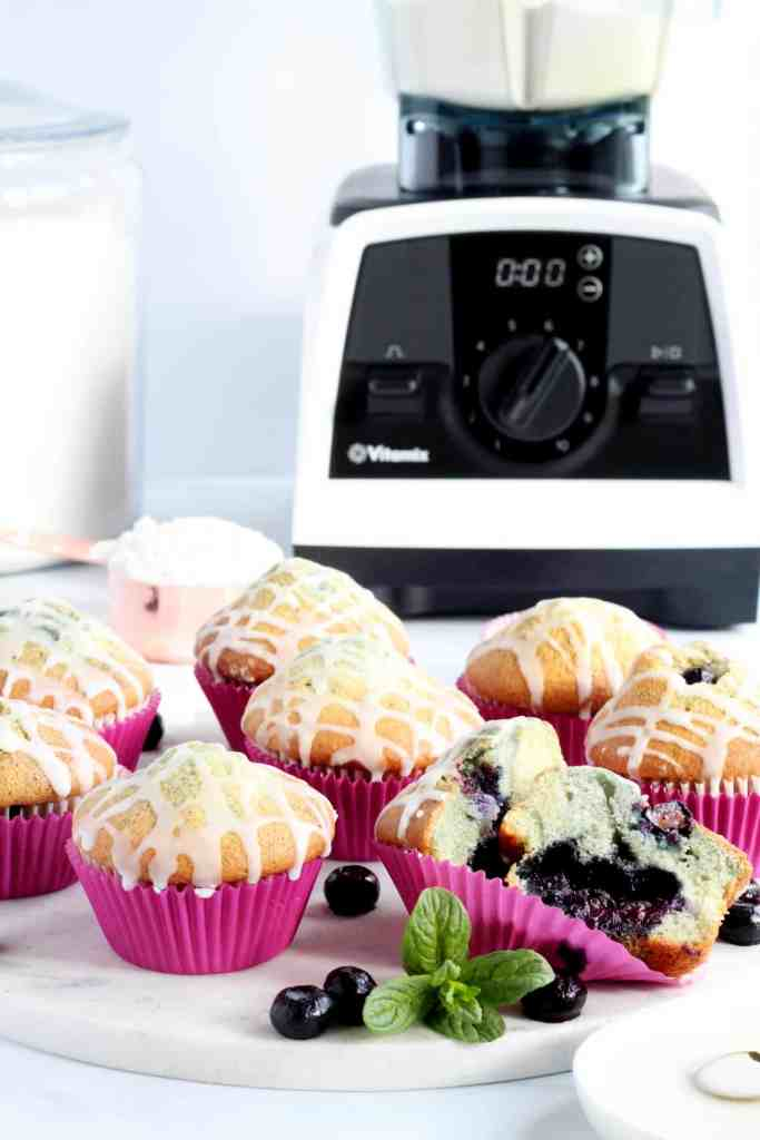 Many bluberry muffins laying on marble board with Vitamix blender