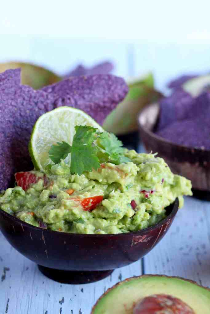 Guacamole dip in wooden bowl with corn chips