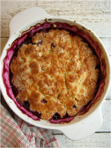 over head view of a baked raspberry blueberry pudding cake