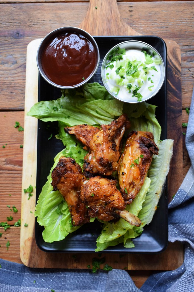 wings on a plate with two dipping sauces