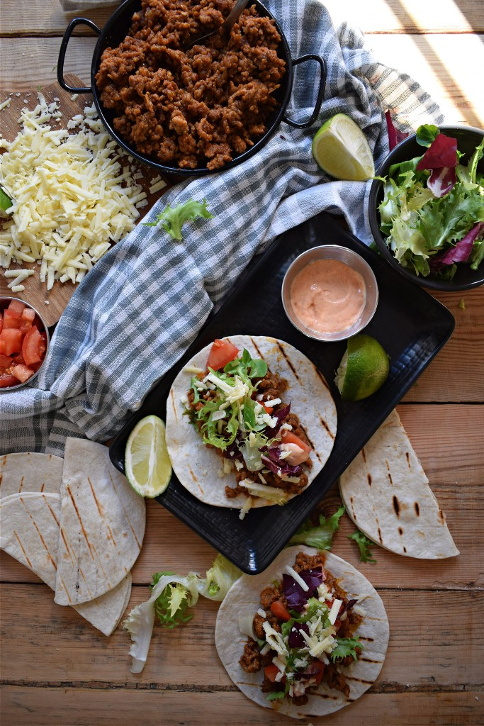 over head table setting view of  Pork tacos with sriracha mayo
