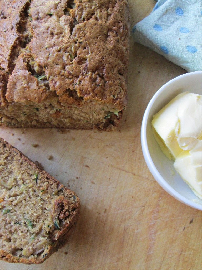zucchini loaf bread on a cutting board with butter