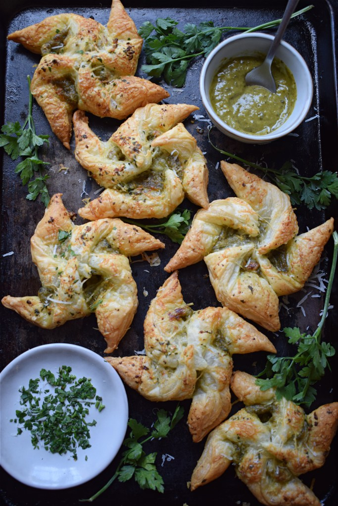 Pesto Puff Pastry Pinwheels on a baking tray with pesto and herbs
