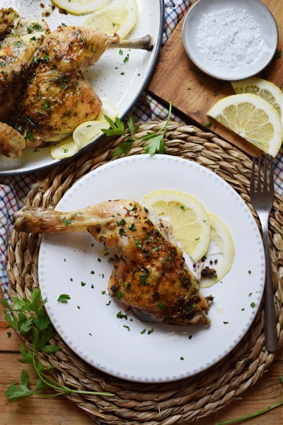 leg of the roasted spatchcock chicken on a plate