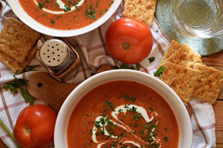 over head table setting view of the slow cooker tomato soup with fresh tomatoes and cream
