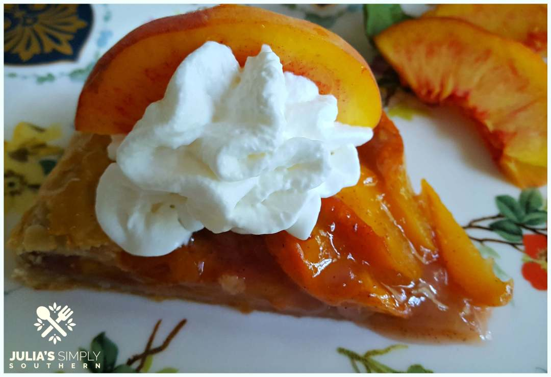 Slice of peach galette with whipped cream and a slice of fresh peach for garnish on a Vanderbilt china plate