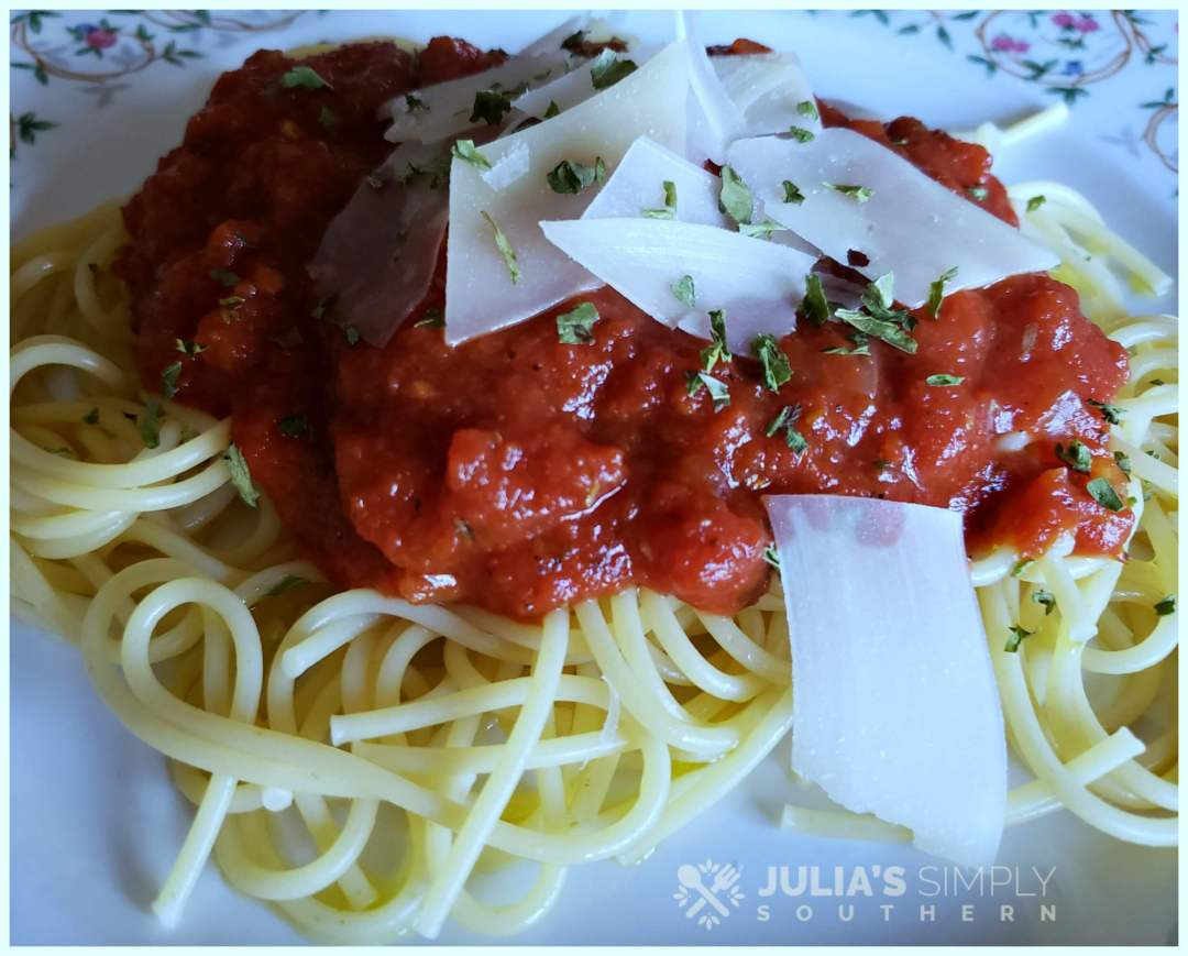 Spaghetti with marinara and Parmesan on a floral china plate garnished with parsley
