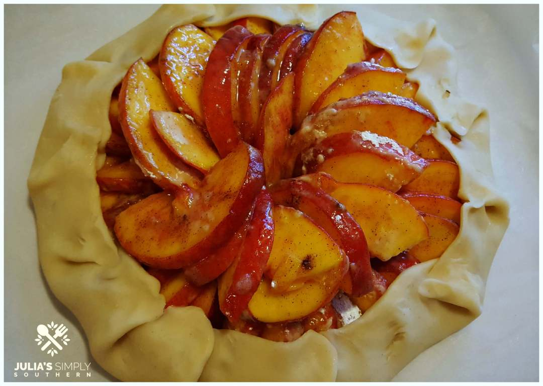 wrapping peaches in pie crust to make a galette dessert