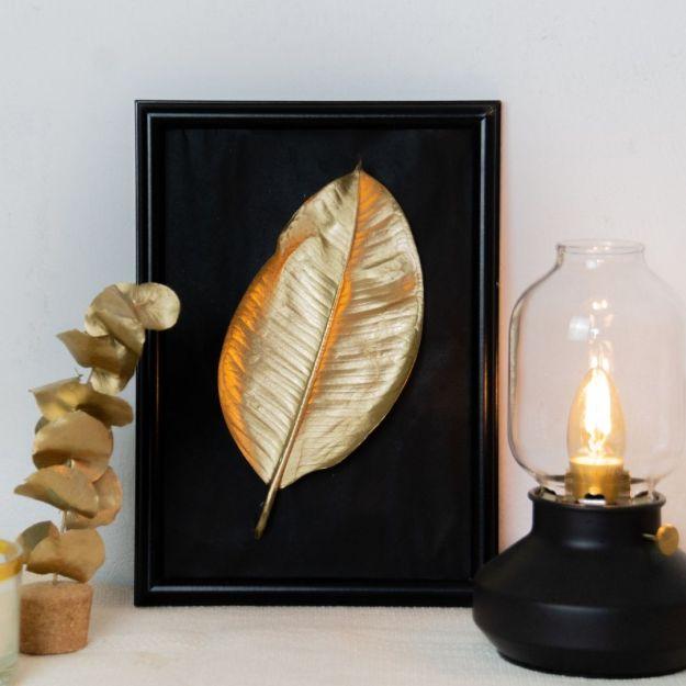 DIY Wanddeko in gold aus Naturmaterialien basteln. goldenes Blatt auf schwarzen Hintergrund eingerahmt in Bilderrahmen.