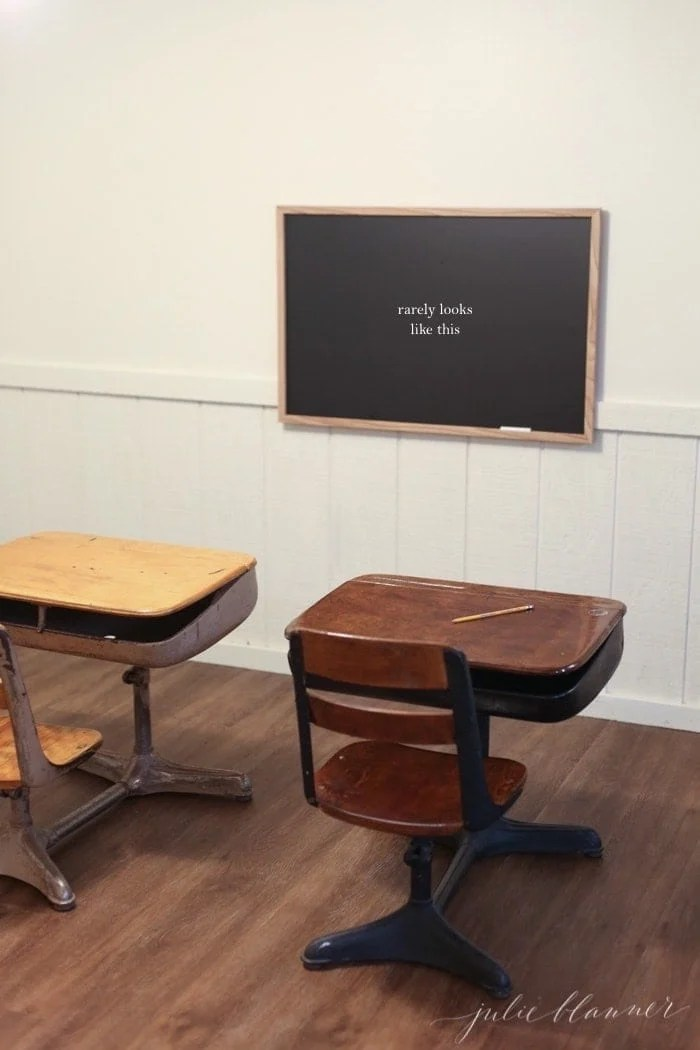 A minimalist living inspired basement for kids, with vintage school desks, a chalkboard and wood floors.