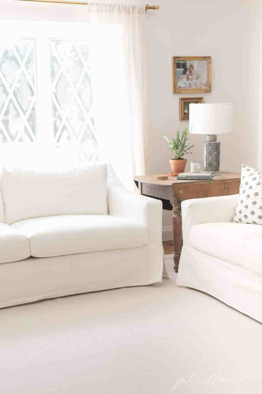 Two white sofas in a neutral living room.
