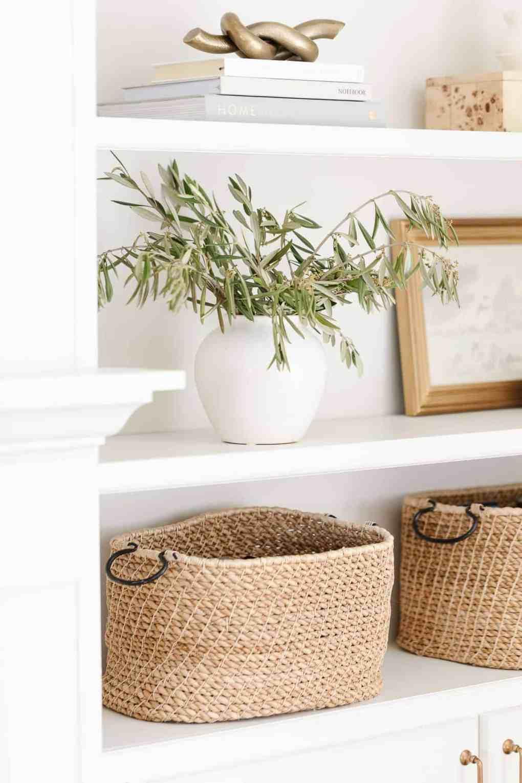Bookshelf decor ideas of baskets, white pottery and artwork on white built ins.