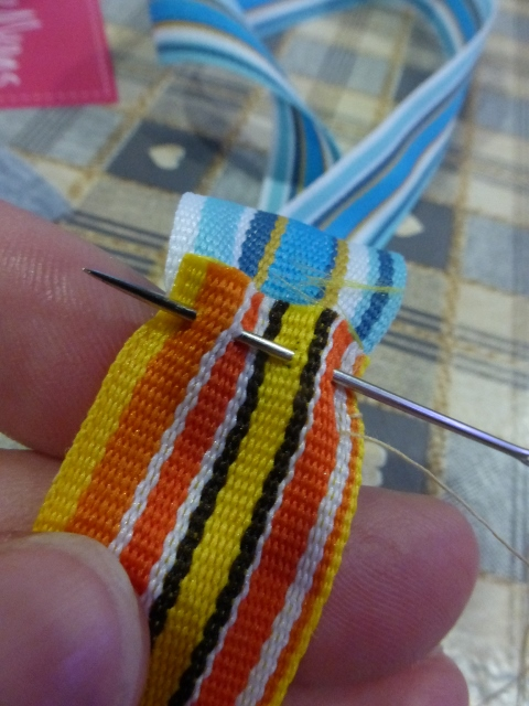 Yellow ribbon and blue ribbon stitched together at short ends