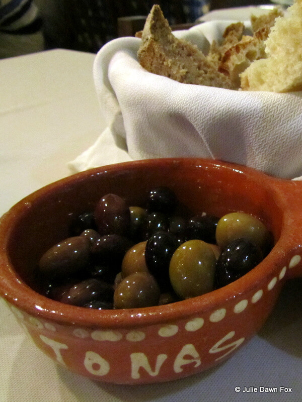 multicoloured Portuguese olives and a basket of bread
