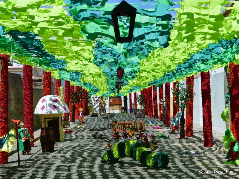 A canopy of green and blue tissue paper above a street decorated with paper toadstools and catapillars