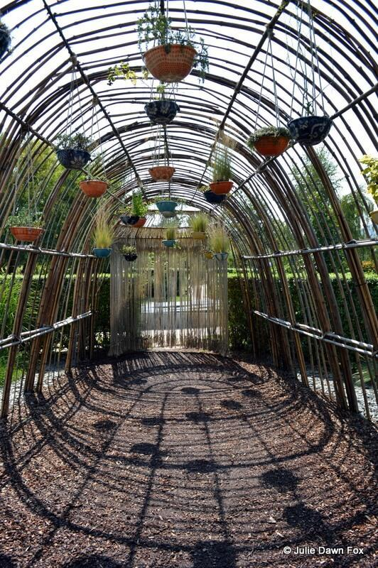 tunnel of shadows and bamboo with hanging baskets