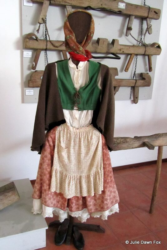 Traditional dress for a Portuguese farming woman with simple ox yokes on the wall
