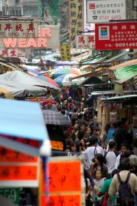Crowded streets of Hong Kong, filled with shops and people.