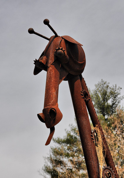 A giraffe made out of different metal parts