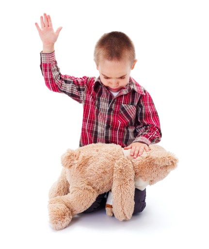 A little boy is spanking his teddy bear, which is turned over his knee.