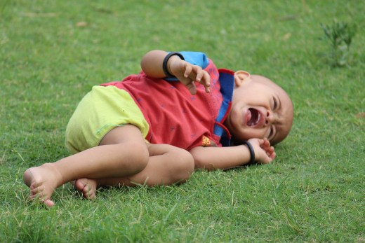Toddler-aged boy is lying on the ground, appearing to be upset and crying
