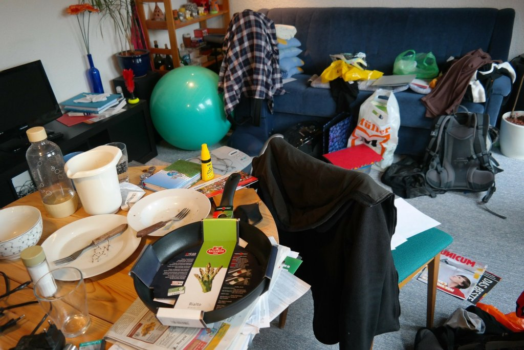 A room with dishes, clothes, toys and other stuff that needs decluttering.