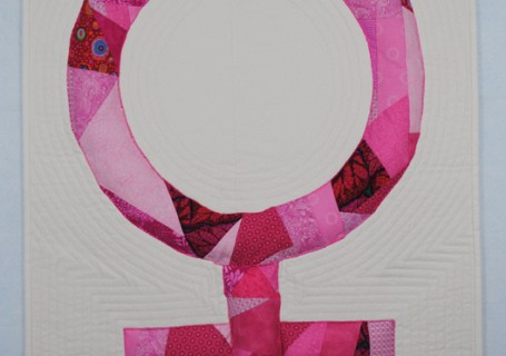art quilt of pink crazy pieced woman symbol on white background