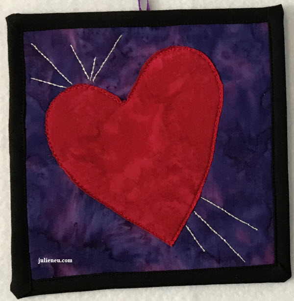 "Small quilted art piece reflecting ""joy"". Red heart on purple background with silver thread lines emanating from heart on left lobe and bottom."